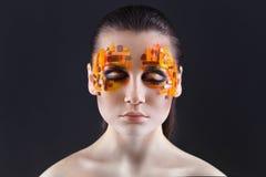Orange och röda bergkristaller på en flickaframsida Arkivfoto