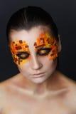 Orange och röda bergkristaller på en flickaframsida Arkivbild