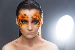 Orange och röda bergkristaller på en flickaframsida Royaltyfri Foto
