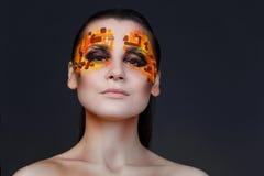 Orange och röda bergkristaller på en flickaframsida Royaltyfria Foton