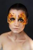 Orange och röda bergkristaller på en flickaframsida Royaltyfria Bilder