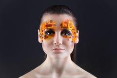 Orange och röda bergkristaller på en flickaframsida Royaltyfri Bild