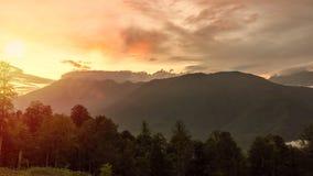 Orange och rosa solnedgång över dalen som omges av berg och skogen royaltyfri foto