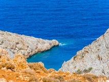 Orange och vita klippor och djupblått hav arkivfoton
