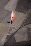 Orange och vitt paragliderpilotflyg ovanför huvudvägdurinen Royaltyfri Bild