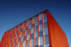 Orange office block. An orange office block standing out strongly against a clear blue sky Stock Images