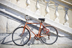 Orange old bicycle against a marble wall Royalty Free Stock Photos
