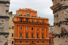 Orange old building in Rome. Architecture, ancoent, ancinte, ancient, facade, side, fornt, doors, windows, balcony, green, clouds, grey, travel, tourism royalty free stock photography