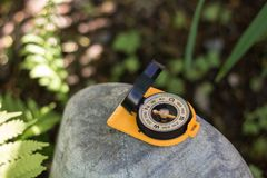 Orange old compass on a wild stone in the forest on a sunny day. The concept of finding the way and navigation. Old Compass on a wild stone in the forest. The royalty free stock photo