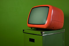 Orange old retro television. On green box in green room Stock Photo
