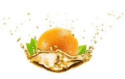 Orange in orange juice splash isolated on the white background.  Stock Photos