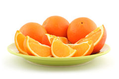 Orange and orange slices. On green plate stock photos