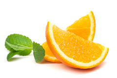 Orange, orange slices and mint leaves. Juicy ripe orange, orange slices and mint leaves on a white background Royalty Free Stock Images