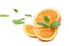 Orange, orange slices and mint leaves. Juicy ripe orange, orange slices and mint leaves on a white background Royalty Free Stock Photos