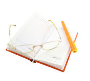 Orange organiser. Glasses and orange pen lie on open diary. It is isolated on a white background Stock Images