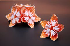 Orange origami flowers made of polka dotted paper. stock photography