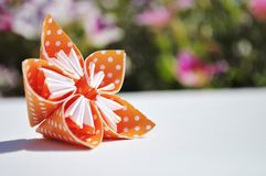 Orange origamiblomma på blom- bakgrund kopiera avstånd Royaltyfria Foton