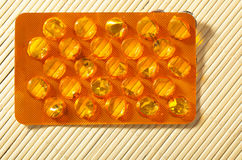 Orange package of pills tablets drug medicine. Health care. Stock Photos
