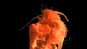 Orange paint in super slow motion splashing. Against a black background stock video