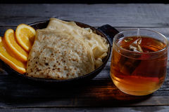 Orange with pancakes. On wooden boards, covered with red cellar mysterious light Stock Image