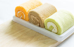 Orange,pandan, chocolate roll cake on wood Royalty Free Stock Image