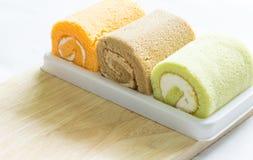 Orange,pandan, chocolate roll cake on wood Royalty Free Stock Image