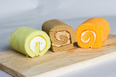 Orange,pandan, chocolate roll cake on wood Royalty Free Stock Photography