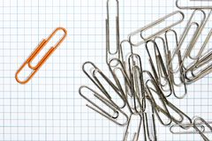Orange paper clip with silver paper clips. On a grilled background Royalty Free Stock Photo