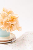 Orange paper flower in small glass with fabric background Stock Photo