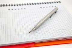 orange paper penna för anteckningsbok Arkivbild