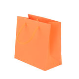 Orange paper shopping bag isolated Stock Images