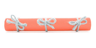 Orange paper tube tied with cord, three natural knots isolated. Orange paper tube tied with cord, three natural knots, isolated stock image
