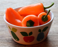 Orange paprikas in a colorful bowl Royalty Free Stock Photography