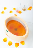 Orange paraffin wax in bowl. Manicure in beauty spa salon. Royalty Free Stock Photo