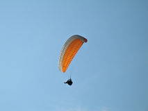 Orange Paraglide. A paraglider is flying in the blue sky with his colourful paraglide Royalty Free Stock Photography