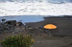 Orange paraply på stranden Arkivbilder