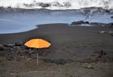 Orange paraply på stranden Arkivbild