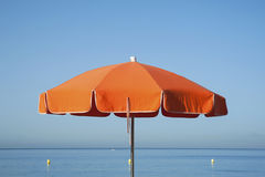 Orange parasol. Orange beach umbrella with the calm ocean and clear blue sky in the background Royalty Free Stock Photo