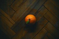 Orange on Parquet. Just an ordinary orange on an old parquet Stock Photo