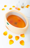 Orange parrafin wax in bowl. Manicure in beauty spa salon. Royalty Free Stock Photo