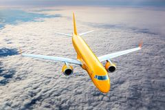 Orange passenger plane in flight. Aircraft flies high in the blue sky over clouds. View from above Stock Photo