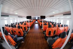 An orange passenger seat in a passenger boat. With life vest stock photo