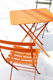 Orange patio chair and table with shadow Royalty Free Stock Photo