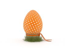 Orange pattern painted easter egg. In green grass with a basket. Easter symbol Stock Images