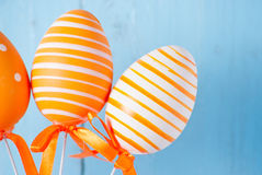 Orange patterned easter eggs on blue background Royalty Free Stock Image