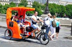 Orange Pedicab i Paris Royaltyfri Foto