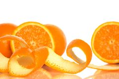 Orange peel and juicy oranges. Spiral orange peel and juicy oranges on white background Royalty Free Stock Photo