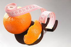 Orange peel and measuring tape. On glassy background royalty free stock photos
