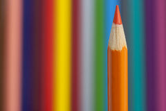 Orange pencil. On multicolored background stock images