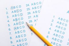 Orange pencil on answer sheets. Top view royalty free stock photo